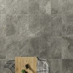 Eikon Exterior tile in the finish Titanio with table and chairs