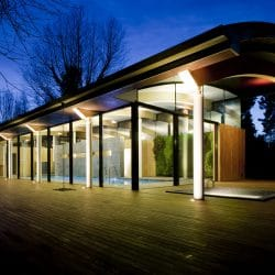 Nighttime view of contemporary hardwood decking wrapping pool house