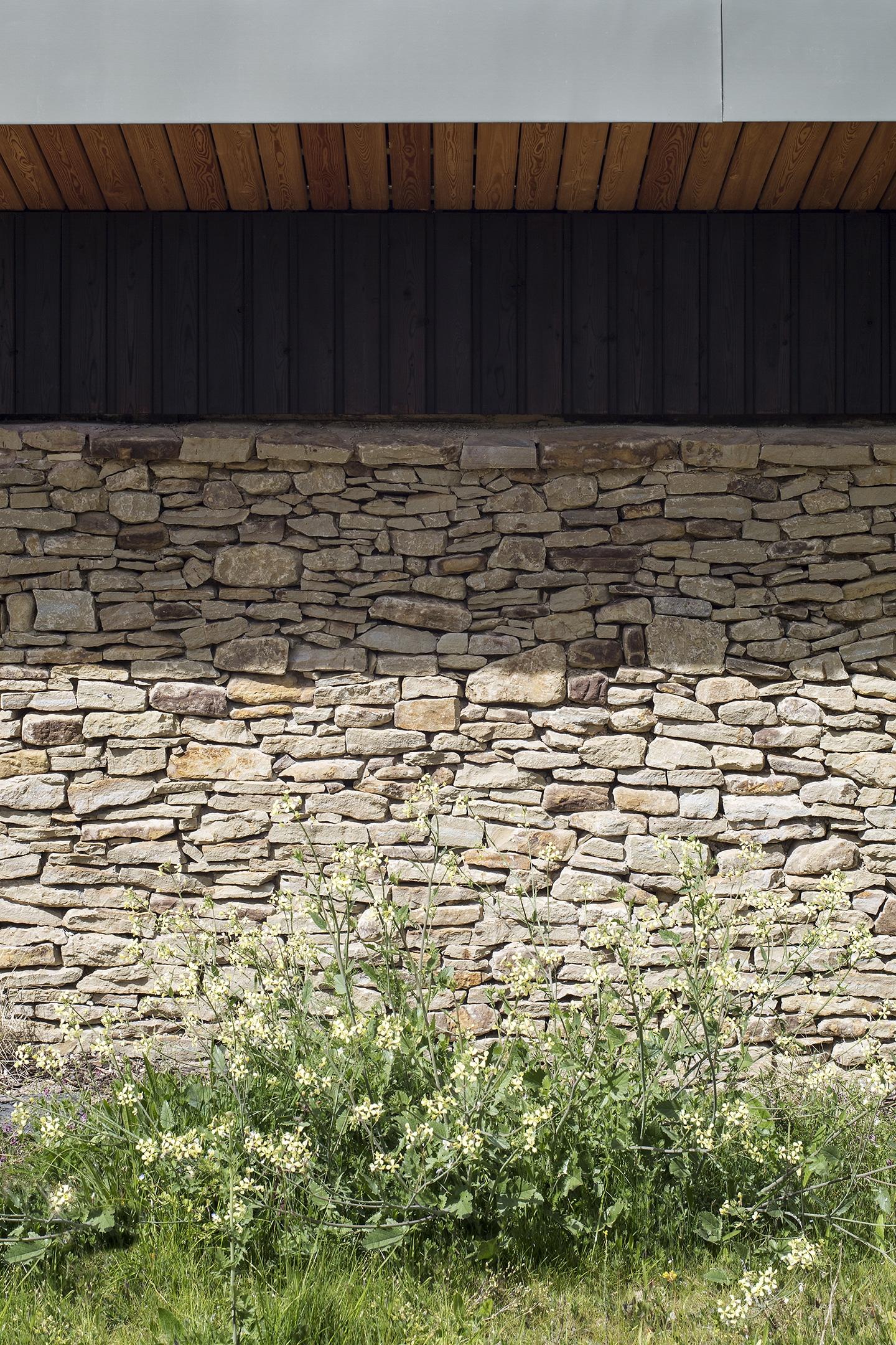 Koshikijima shou sugi ban cladding close up next to natural stone cladding
