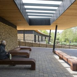 Man eating soup sat surrounded by Shou sugi ban charred timber cladding and untreated siberian larch cladding